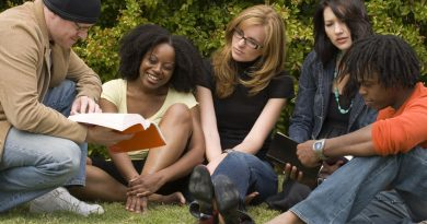 Group of young people outside gathering around a book
