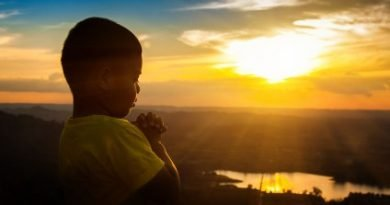 Young boy praying with the sun shining bright